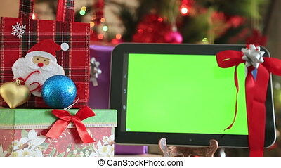 Green screen digital tablet with gift box and christmas tree...