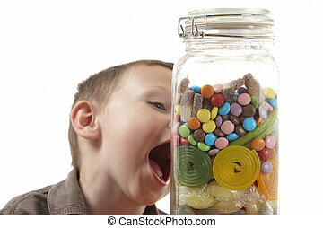 young boy and candy jar - young boy showing expression of...