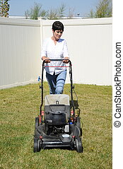Yardwork outdoors - Mature female beauty mowing the lawn...