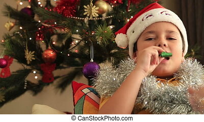 Happy boy with santa hat sitting in front of Christmas tree