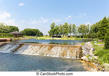 Beautiful lake with waterfall in green park in the spring