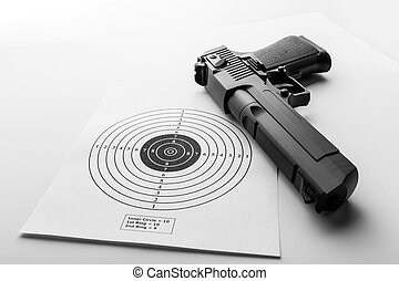 Paper target and pistol on white background