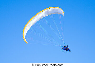 Yellow paraglider in serene cloudless blue sky