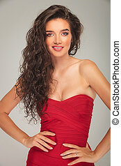 model in red dress touching her waist while posing - busty...