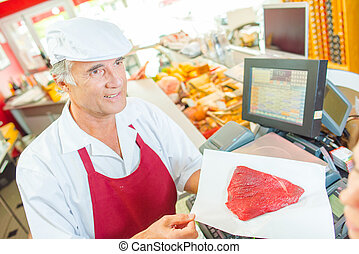 Butcher presenting a cut of beef to a customer