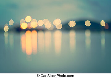 Colorful city lights with bokeh effect reflected over sea...