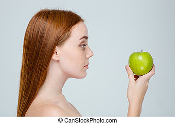 Side view portrait of a woman holding apple