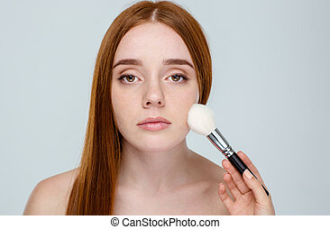 Redhair woman using makeup brush - Portrait of a young...