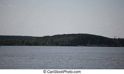 Sailing boat in the background of the forest. Summer