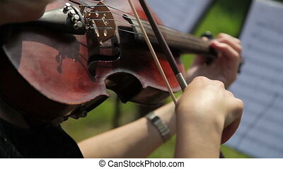 A female musician playing a violin in an orchestra Close-up