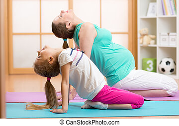 Beautiful pregnant woman with elder child daughter doing gym fitness exercise