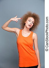 Young emotional woman with finger to her temple like gun -...