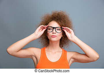 Confident young female with voluminous curly hairstyle in...