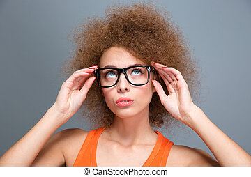Concentrated young curly woman in black glasses looking up -...