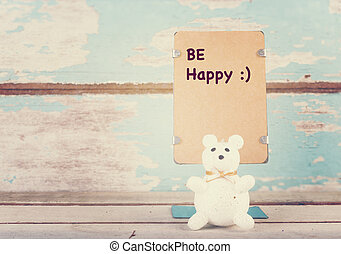 Be happy wrote paper stand and cute bear on grunge blue...