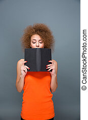 Concentrated girl with voluminous curly hairstyle reading a...