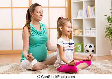 Pregnant mother and child do yoga, relax in lotus position on fit mat at home