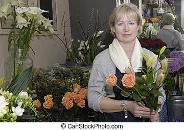 Florist holding a bouquet of flowers in her shop