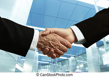 business - hand shake of businessmen on corporate building...