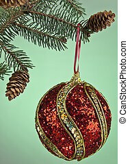 branch of christmas tree and ball on a green background