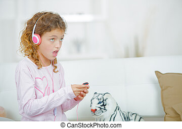 Little girl listening to music through headphones