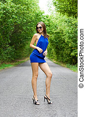Beautiful woman in blue dress posing on the road