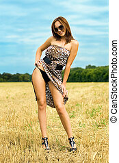 Playful young woman - Pretty woman in the field wearing...