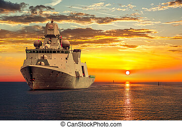 Warship - The military ship on sea at sunrise.