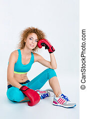 Sports woman in boxing gloves sitting on the floor -...