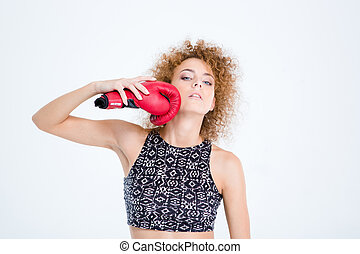Woman with curly hair holding boxing glove - Portrait of a...