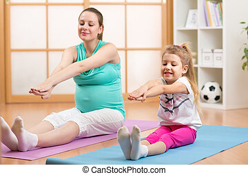 Pregnant woman with her first child doing gymnastics -...