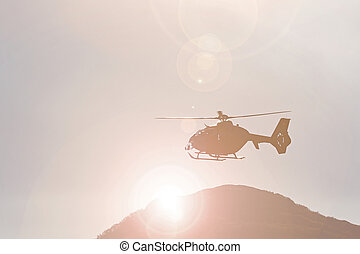 Backlit helicopter in flight - Mountain rescue helicopter...