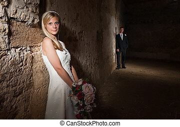 Wedding in an old barn - Bride in white posing against a...