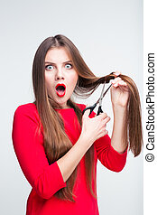 Portrait of a shocked woman cutting her hair isolated on a...