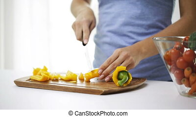 smiling young woman chopping pepper at home - healthy...