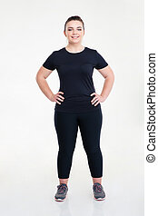 Portrait of a happy fat sports woman standing isolated on a...