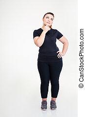 Pensive fat woman in sportswear looking up