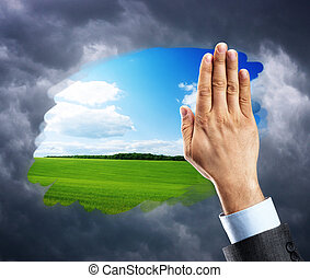 Hand cleaning window with blue sky