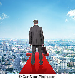 Businessman on red arrow above city