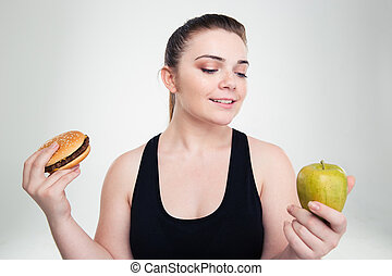 Fat woman choosing between burger or apple
