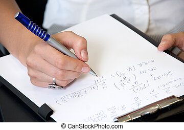 Student in classroom writing mathematics formulas