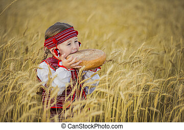 Child in Ukrainian national costume with a loaf of bread in...