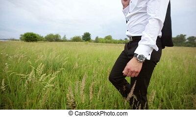 Man in a suit walks in the field