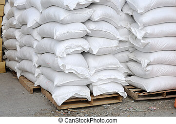 Stacked white sacks at storehouse