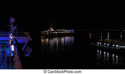 a ferry boat by night - lighted large ship at night near a...