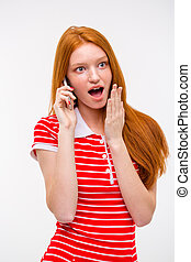 Amazed excited redhead woman talking on mobile phone -...