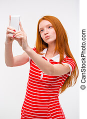 Young beautiful redhead woman taking selfie and making duck...