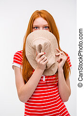Embarrassed shy woman hiding her face behind hat -...