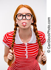 Funny amusing girl in round glasses showing tongue - Redhead...