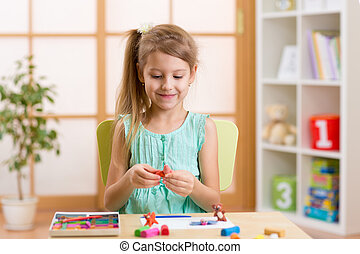 Kid playing modeling plasticine or molding clay - Kid girl...